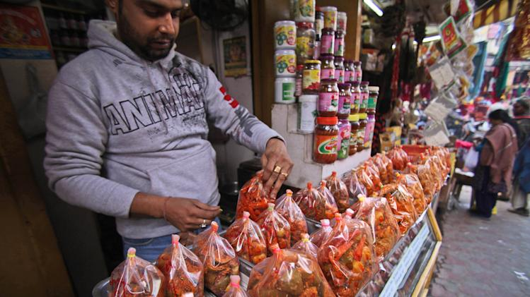 An Indian shopkeeper displays pickles, a spicy food item, for sale at a retail tore in Jammu, India, Friday, Dec. 7, 2012. India's parliament on Friday approved the government's plans to open up the country's massive retail sector to international big-box companies such as Wal-Mart. (AP Photo/Channi Anand)