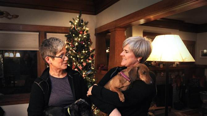 """Former Army Major Margaret Witt, right, and Lori Johnson, left, stand in their south hill home, Monday, Dec. 3, 2012 in Spokane, Wash. They are planning to marry in a few weeks after receiving one of the first marriage licenses for same sex couples this week. Witt fought the Army over """"Don't Ask, Don't Tell"""" and was with President Obama when he signed the repeal.  (AP Photo/The Spokesman-Review, Jesse Tinsley)  COEUR D'ALENE PRESS OUT   MBI"""
