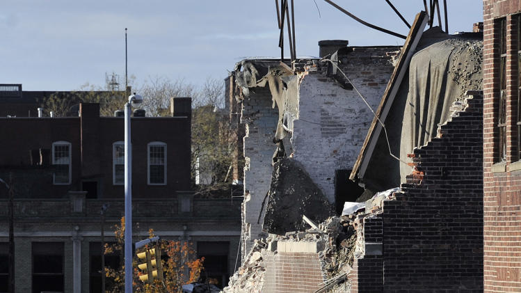 People keep a perimeter, Saturday, Nov. 24, 2012, around the area where a gas explosion leveled a strip club in Springfield, Mass., on Friday evening. Investigators were trying to figure out what caused the blast where the multistory brick building housing Scores Gentleman's Club once stood. (AP Photo/Jessica Hill)