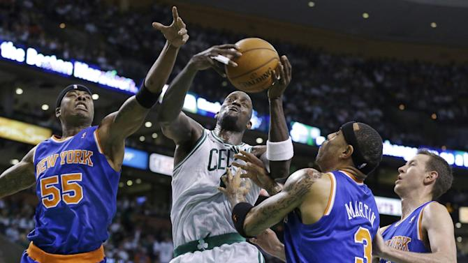 Boston Celtics center Kevin Garnett, second from left, pulls down an offensive rebound against New York Knicks forward Quentin Richardson (55), forward Kenyon Martin (3) and forward Steve Novak (16) during the first half in Game 4 of a first-round NBA basketball playoff series in Boston, Sunday, April 28, 2013. (AP Photo/Elise Amendola)