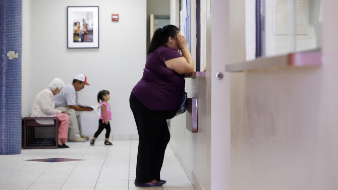 In this July 12, 2012 photo, a woman stands at the registration window at Nuestra Clinica Del Valle in San Juan, Texas. About 85 percent of those served at the clinic are uninsured. Texas already has one of the nation's most restrictive Medicaid programs, offering coverage only to the disabled, children and parents who earn less than $2,256 a year for a family of three. Without a Medicaid expansion, the state's working poor will continue relying on emergency rooms _ the most costly treatment option _ instead of primary care doctors. The Texas Hospital Association estimates that care for uninsured patients cost hospitals in the state $4.5 billion in 2010. (AP Photo/Eric Gay)