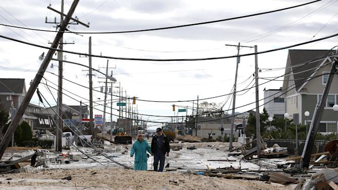 FILE - In this Wednesday, Oct. 31, 2012 file photo, Robert Bryce, right, walks with his wife, Marcia Bryce, past downed utility poles and other debris from Superstorm Sandy on Route 35 in Seaside Heights, N.J. An Associated Press analysis of outage times from other big hurricanes and tropical storms suggests that, on the whole, the utility response to Sandy, especially in hardest-hit New York and New Jersey, was typical - or even a little faster than elsewhere after other huge storms. (AP Photo/Julio Cortez, File)