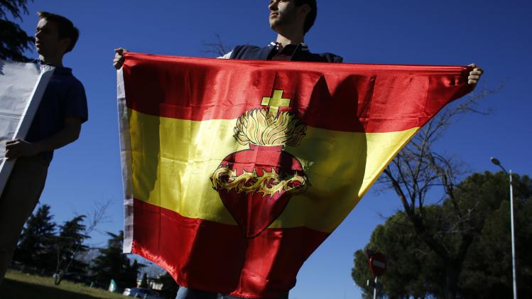 "A member of the Social Christian Party holds an Spanish flag with a ""Heart of Jesus"" during a protest against the abortion law in Madrid"