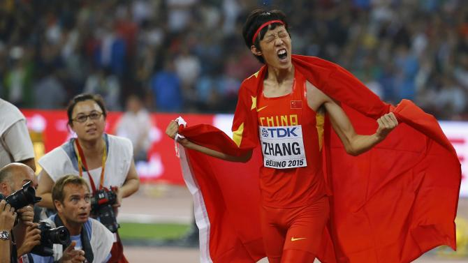 Second placed Zhang of China celebrates with a national flag after winning silver in the men's high jump final during the 15th IAAF World Championships at the National Stadium in Beijing