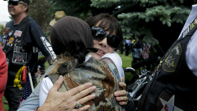 """Jani Bergdahl, center, mother of captive U.S. Army Sgt. Bowe Bergdahl, gets a hug from a well-wisher at the """"Bring Bowe Back"""" celebration held to honor Sgt. Bergdahl in Hailey, Idaho, Saturday, June 22, 2013. The father and mother of the only known U.S. prisoner of war plan to speak on Saturday afternoon to a big crowd in their central Idaho hometown just days after his Taliban captors announced they want to exchange him for prisoners being held at Guantanamo Bay. (AP Photo/Jae C. Hong)"""