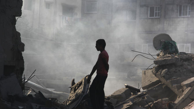 A Palestinians looks for his belongings after a house was destroyed in an Israeli strike in Rafah, southern Gaza Strip, Saturday, Aug. 2, 2014. Israel bombarded Rafah on Saturday as troops searched for an officer they believe was captured by Hamas in an ambush that shattered a humanitarian cease-fire and set the stage for a major escalation of the 26-day-old war. (AP Photo/Hatem Ali)