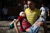 A man carries the body of a child who was wounded during shelling by Syrian government forces, near a bakery in the Tariq al-Bab district of the northern city of Aleppo. The shell struck the side of a building killing around ten people, and wounding at least 20 more as they queued to buy bread in the street below