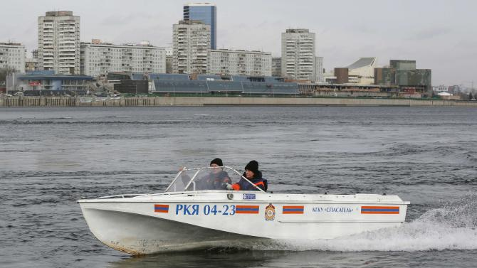 Rescuer Borisova operates a motorboat during a training session in Krasnoyarsk