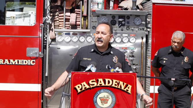 Art Hurtado, Pasadena Fire captain and paramedic takes questions during a news conference in Pasadena, Calif., Thursday, April 11, 2013. At right, Calvin Wells Pasadena Fire Chief. Hurtado helped save the life of a man at Home Depot after the victim apparently tried to cut his arms off using handsaws found at the home improvement store in West Covina, Calif. With help from police and store employees, Hurtado who was off-duty collected rope and rags from store shelves and put makeshift tourniquets on both arms, most likely saving the man's life, police said. (AP Photo/Damian Dovarganes)