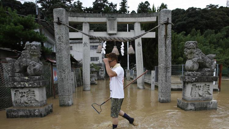 A local resident walks past the front of traditional torii gate at a partially submerged shrine where a landslide swept through a residential area at Asaminami ward in Hiroshima