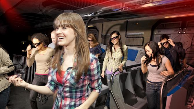 """In this undated image released by Universal Studios Hollywood, riders exit the """"Transformers the Ride: 3D,"""" attraction at Universal Studios Hollywood in Los Angeles. Debuting May 25 at Universal Studios Hollywood, the ride, based on the film franchise, offers motion-simulator vehicles and 3D high definition video. (AP Photo/Universal Studios Hollywood)"""