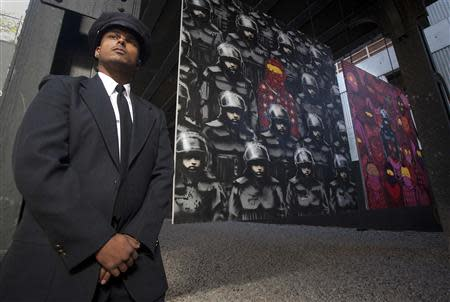 A security guard stands beside a new installation of British graffiti artist Banksy in New York