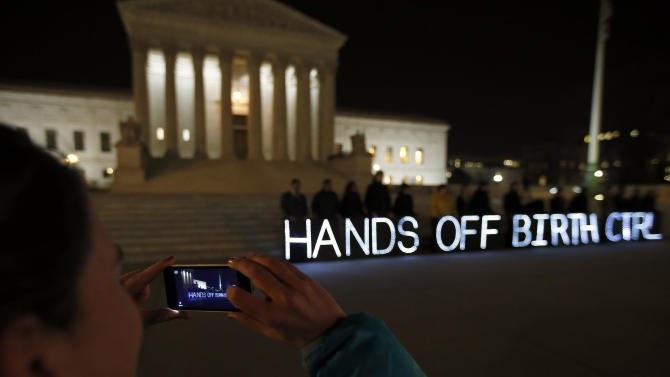 An organizer takes a a picture of a group of people organized by the NYC Light Brigade and the women's rights group UltraViolet, as they use letters in lights to spell out their opinion, in front of the Supreme Court, Monday, March 24, 2014, in Washington. The Supreme Court is weighing whether corporations have religious rights that exempt them from part of the new health care law that requires coverage of birth control for employees at no extra charge. (AP Photo/Alex Brandon)
