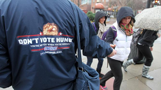 """IMAGE DISTRIBUTED FOR MARS CHOCOLATE NORTH AMERICA - In this image released on Wednesday, Nov. 7, 2012, voters are given a SNICKERS® candy bar on the way to the polls in Iowa City, Iowa as part of SNICKERS """"Don't Vote Hungry"""" campaign. SNICKERS launched the campaign to remind everyone of the importance of this year's election and to not vote hungry, because """"You're not you when you're hungry®"""". (Conrad Schmidt/AP Images for Mars Chocolate North America)"""