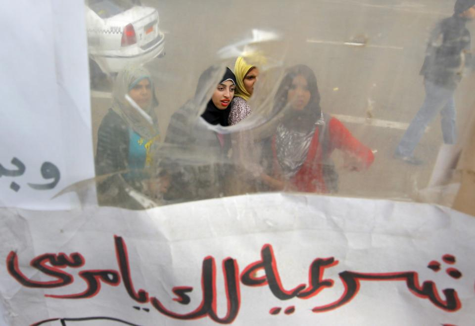 "Egyptians read slogans on a poster displayed in a temporary exhibit of revolutionary paraphernalia in Tahrir Square in Cairo, Sunday, Dec. 30, 2012. Arabic reads, "" Morsi, you don't have any legality."" (AP Photo/Amr Nabil)"