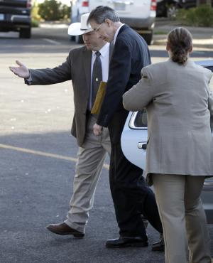"Law enforcement officials, left, and right, help polygamist religious leader Warren Jeffs out of a vehicle as he arrives at the Tom Green County Courthouse Thursday Aug. 4, 2011, in San Angelo, Texas.  Jeffs, 55, is  accused of sexually assaulting two girls he took as brides during so-called ""spiritual marriages.""   (AP Photo/Tony Gutierrez)"