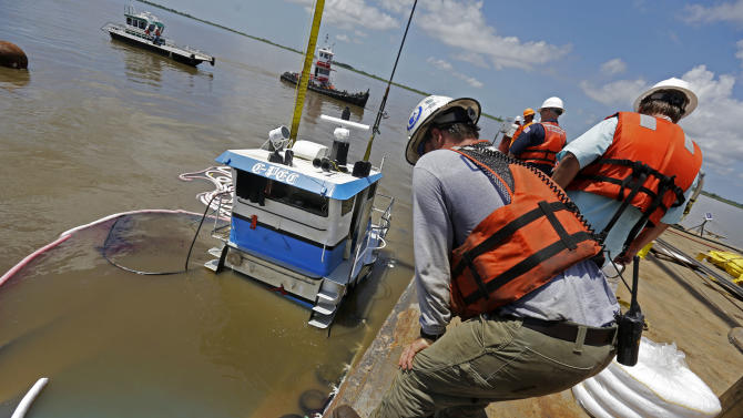 """Workers raise """"C-Pec,"""" the 47-foot tugboat which sank Saturday in the middle of the Mississippi River, near Venice, La., Wednesday, July 10, 2013. (AP Photo/Gerald Herbert)"""