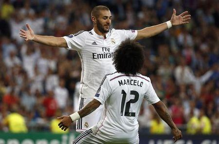 Real Madrid's Benzema celebrates with his teammate Marcelo after scoring a goal against Basel during their Champions League soccer match in Madrid