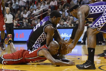 Miami Heat's Allen scrambles for loose ball with Sacramento Kings' Salmons and Cousins during their NBA basketball game in Miami
