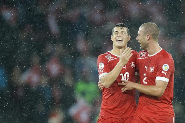 Switzerland's Granit Xhaka, left, and Switzerland's Pajtim Kasami, right, celebrate after winning the FIFA World Cup 2014 group E qualifying soccer match between Switzerland and Slovenia at the Stade