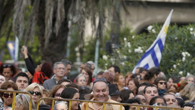 People with masks depicting Uruguay's President Jose Mujica participate in a ceremony where Mujica will receive the Uruguayan flag on the last working day of his term in Montevideo