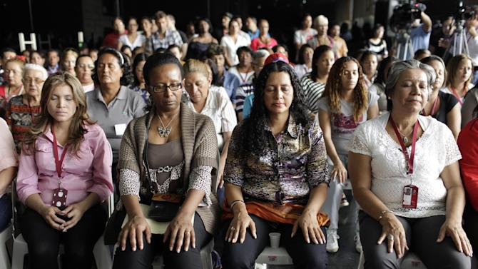 Supporters of Venezuela's President Hugo Chavez pray for his health during a Mass at the Ministry of Education headquarters in Caracas, Venezuela, Tuesday, Feb. 19, 2013. Chavez is back in Venezuela after 10 weeks of cancer treatment in Cuba, but he remained silent and out of sight on Tuesday, closed away in a tightly guarded military hospital, leaving the nation to speculate about whether he can still govern, and for how long. (AP Photo/Ariana Cubillos)