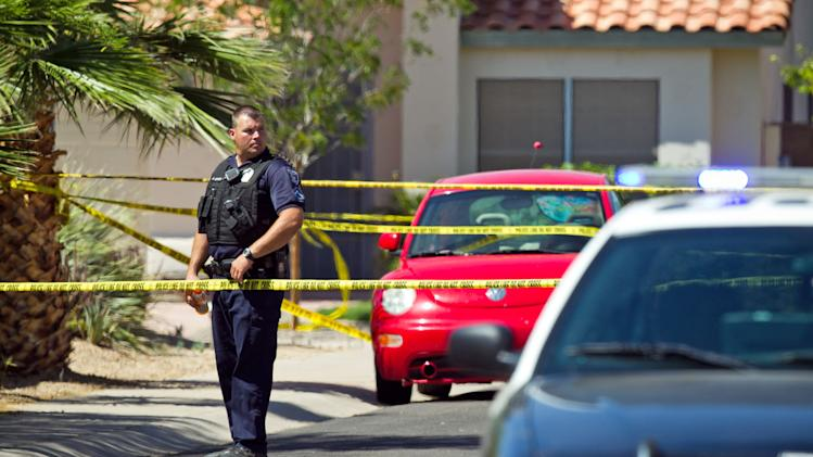 Police officers stand outside a house after a shooting, where police say a man shot and killed four people, including a toddler, before killing himself, in Gilbert, Ariz., on Wednesday, May 2, 2012. Police say the man was armed with several firearms, and officers recovered two handguns and a shotgun. (AP Photo/The Arizona Republic, Michael Schennum)