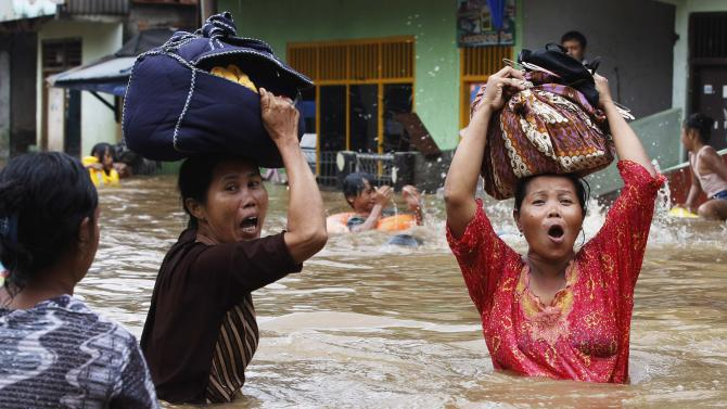 File photo of women reacting as they flee from their flooded area in Jakarta