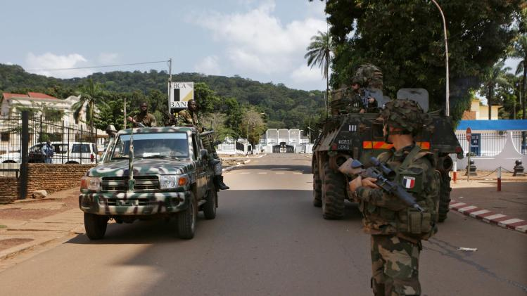 Seleka soldiers drive past French soldiers on patrol in Bangui
