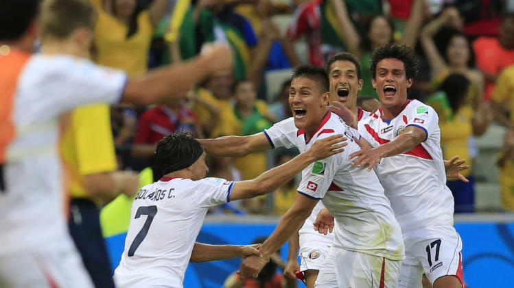 Costa Rica's Oscar Duarte, center, celebrates after scoring his side's second goal during the group D World Cup soccer match between Uruguay and Costa Rica at the Arena Castelao in Fortaleza, Brazil, Saturday, June 14, 2014. (AP Photo/Bernat Armangue)