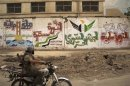 A Free Syrian Army fighter rides a motorbike past revolutionary graffiti on a wall in Deir al-Zor