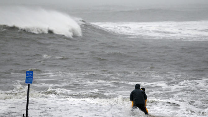 Two men wade in the rough Atlantic Ocean Monday Oct. 29, 2012, in Cape May, N.J., as Hurricane Sandy continues toward landfall. Hurricane Sandy continued on its path Monday, as the storm forced the shutdown of mass transit, schools and financial markets, sending coastal residents fleeing, and threatening a dangerous mix of high winds and soaking rain.  (AP Photo/Mel Evans)