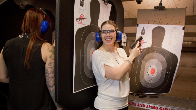 Tanya Morris, right, poses for a photo with her shot-up target after getting married at the Guns and Ammo Garage, Thursday, Feb. 14, 2013, in Las Vegas. Las Vegas is embracing tourists' newfound interest in big guns the only way it knows how: by going all in. The shooting range and gun store offered free vow renewals and wedding ceremonies  throughout the day on Thursday. (AP Photo/Julie Jacobson)