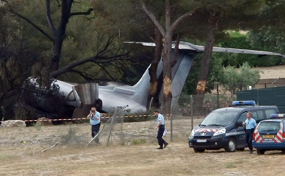 Police Officers work near plane that crashed on landing at Le Castellet airport, near Toulon, southern France, Friday, July, 13, 2012. Three US citizen died in the accident. (AP Photo/Claude Paris)