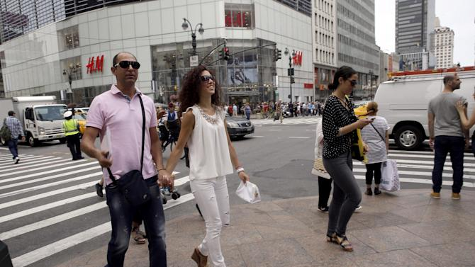 """Newlyweds Valasia Limnioti, right, and Konstantinos Patronis walk along 34th Street and 6th Avenue in Midtown Manhattan, Thursday, July 2, 2015, in New York. The couple topped """"the dream trip of our lives"""" in New York City, where their three-week honeymoon turned into a nightmare: Their Greek-issued credit cards were suddenly declined and they were left nearly penniless. Strangers from two Greek Orthodox churches in Queens came to their rescue, giving them survival cash until their flight home to Greece this Friday. (AP Photo/Mary Altaffer)"""
