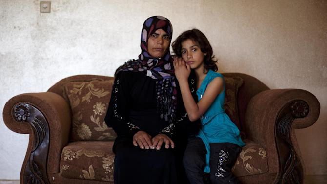 Palestinian woman Sahar Kabaha, 33, sits beside her 10-year-old daughter Nashwa, in the Arab-Israeli town of Bartaa, Wednesday, June 12, 2013. After her Israeli Arab husband died last year, Israel's interior ministry refused to renew her permit to live in the Jewish state, effectively denying her the right to remain in the country, even though her four children are Israeli citizens. She now lives without legal papers and is appealing the decision. For the past decade, Israel has largely restricted Palestinians from joining their spouses inside the Jewish state, citing security concerns like Palestinian militants using entry permits gained through marriage to carry out attacks in Israel. (AP Photo/Dusan Vranic)