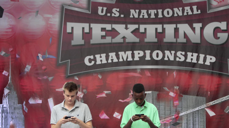 Austin Wierschke, left, of Rhinelander, Wis., and  Kent Augustine, of Jamaica, N.Y., compete during the final round of the 2012 LG U.S. National Texting Championship , Wednesday, Aug. 8, 2012 in New York.  (AP Photo/Mary Altaffer)
