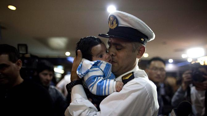 Martin Tejera, member of the crew Argentine ship Libertad, kisses his son Benjamin as he arrives at Buenos Aires airport, Argentina, Thursday, Oct. 25, 2012.  Nearly 300 navy cadets arrived to Argentina's capital from Ghana on an Air France charter hired by the government after Argentina's President Cristina Fernandez refused to negotiate the release of the Argentine naval sailing ship, Libertad. The ship had been held in a port outside Ghana's capital Oct. 2, when a Ghana court ruled to detain the vessel as collateral for Argentina's unpaid debts. (AP Photo/Natacha Pisarenko)