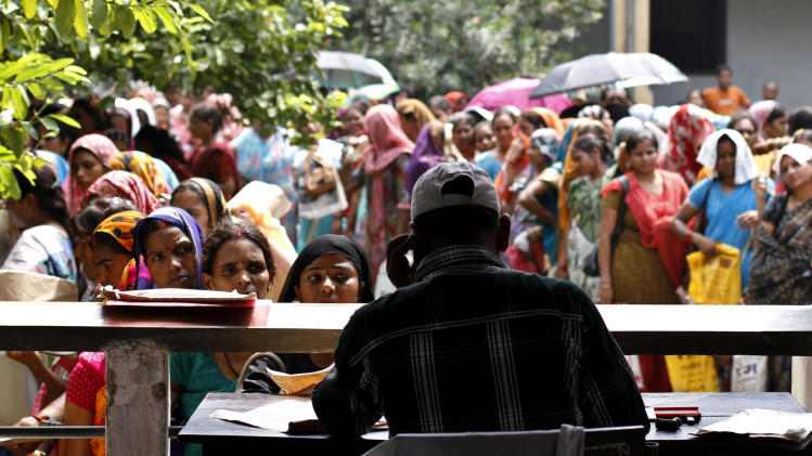 In photo taken Wednesday, Aug. 29, 2012, unemployed educated Indian women stand in queues to register themselves at the Employment Exchange Office in Allahabad, India. India, with the world's largest chunk of illiterates at over 250 million, has to invest heavily in education and skills training, said Ashish Bose, a leading demographer. While millions of job seekers have impressive sounding diplomas, many don't have the skills promised by those certificates from colleges and technical institutes with poor standards. (AP Photo/Rajesh Kumar Singh)