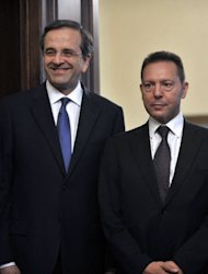 <p>Greek Finance minister Yiannis Stournaras stands with Greek Prime Minister Antonis Samaras at the presidential mansion in Athens on July 5. The new Greek government presents plans to salvage its debt rescue programme on Friday, aiming to appease EU-IMF auditors and gain some room to renegotiate the tough austerity terms with its creditors.</p>