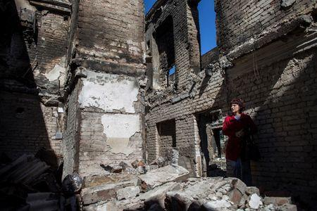 A woman stands inside her destroyed home in the town of Ilovaysk, eastern Ukraine