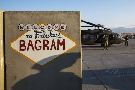 U.S. soldier from the 3rd Cavalry Regiment casts a shadow on a sign painted on a blast barrier at Bagram Air Field in the Parwan province of Afghanistan