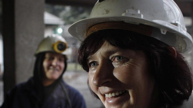 Sakiba Colic, left, and Semsa Hadzo, right,  exchange jokes and laugh outside the shaft of the coal mine in Breza, 20 kms north of Sarajevo, Bosnia, after completing their 8-hour shift at 450 meters under ground on Wednesday, Jan. 16, 2013.  The mine in Breza is the only one in Bosnia where a group of women work deep underground in the coal mines alongside their male colleagues, a legacy of communism, but they're set to retire in three years, marking the end of an era for this community where almost everybody is connected to the coal mine. The shafts and elevators echo with laughter and tales of their grandchildren as women miners work alongside their male counterparts.(AP Photo/Amel Emric)