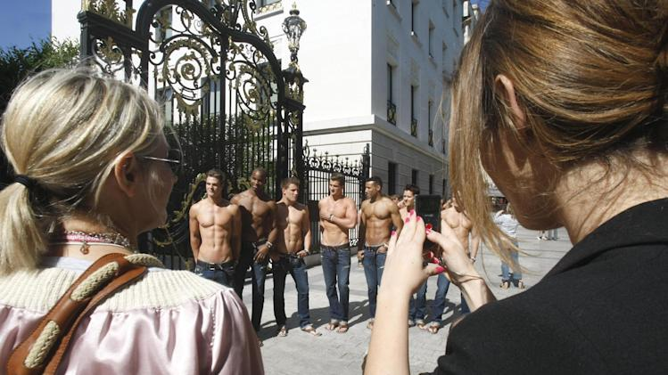 FILE - In this May 12, 2011 file photo, bystanders take snapshots as  bare-chested models pose in front of the Abercrombie & Fitch shop on the Champs Elysees in Paris, a promotion for the opening of the new U.S. brand shop in Paris. Abercrombie & Fitch Co.'s third quarter struggles in Europe caused its share price to plummet. (AP Photo/Remy de la Mauviniere, File)
