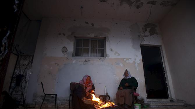An elderly Palestinian man and his wife warm themselves by a fire inside their house damaged during 2014 war, on a stormy day in Beit Hanoun in the northern Gaza Strip