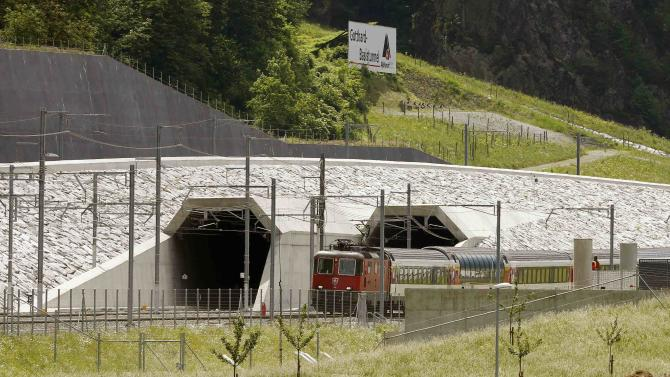A train drives past the northern gates of the NEAT Gotthard Base Tunnel near Erstfeld