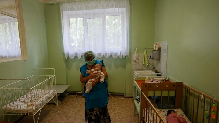 An orphan is carried as another sleeps in a crib in an orphanage in Kramatorsk