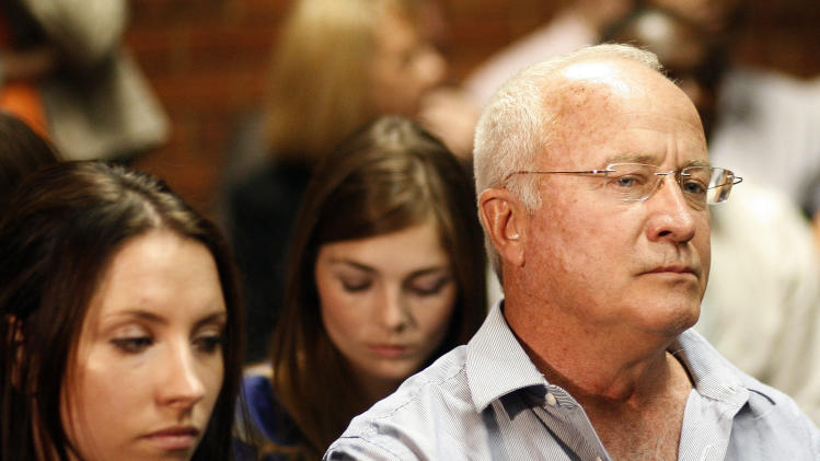 Olympic athlete Oscar Pistorius's father Henke Pistorius, right, with daughter Aimee, left, during his bail hearing at the magistrate court in Pretoria, South Africa, Thursday, Feb. 21, 2013. The lead investigator in the murder case against Pistorius faces attempted murder charges himself over a 2011 shooting, police said Thursday in another potentially damaging blow to the prosecution. Prosecutors said they were unaware of the charges against veteran detective Hilton Botha when they put him on the stand in court to explain why Pistorius should not be given bail in the Valentine's Day shooting death of his girlfriend. (AP Photo/Themba Hadebe)