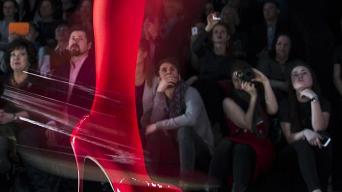 FILE - In this file photo dated  Friday, March 27, 2015, spectators watch as a model displays a creation by Russian designer Slava Zaitsev during Fashion Week, in Moscow, Russia. (AP Photo/Pavel Golovkin, FILE)