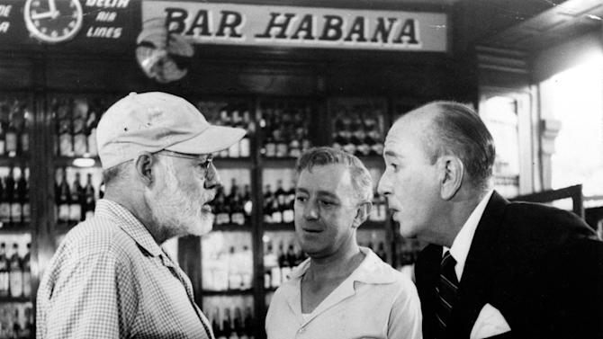 "FILE - In this  May 12, 1959, American novelist Ernest Hemingway, left, speaks with actors Alec Guinness, center, and Noel Coward in Sloppy Joe's Bar during the making of Sir Carol Reed's film version of ""Our Man in Havana,"" based on Graham Greene's best seller, in Havana, Cuba.  Sloppy Joe's will be reopened in February 2013 by the state-owned tourism company Habaguanex, part of an ambitious revitalization project by the Havana City Historian's Office, which since the 1990's has transformed block after block of crumbling ruins into rehabilitated buildings along vibrant cobblestone streets, giving residents and tourists from all over the chance to belly up to the same bar that served thirsty celebrities like Rock Hudson, Babe Ruth and Ernest Hemingway. (AP Photo, File)"